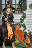 Cute young witch with a broom Royalty Free Stock Image