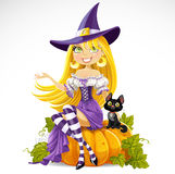 Cute young witch sits on a pumpkin with a familiar Stock Image