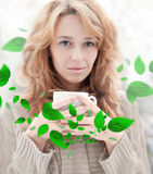 Cute young woman. Portrait of beautiful red hair girl drinking coffee on winter background. Grean leaves are floating around her royalty free stock photo
