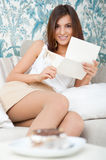Cute young woman. Delighted woman reading a greeting card sitting on the sofa at home stock photos