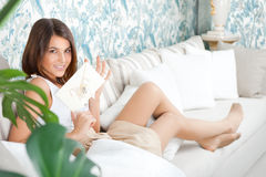 Cute young woman. Delighted woman reading a greeting card sitting on the sofa at home royalty free stock image
