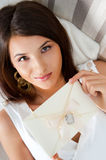 Cute young woman. Delighted woman reading a valentine greeting card with heart and ribbon lying on the sofa at home. Top View stock images