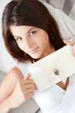 Cute young woman. Delighted woman reading a valentine greeting card with heart and ribbon lying on the sofa at home. Top View royalty free stock image