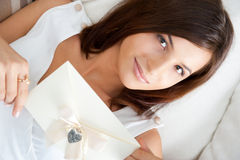 Cute young woman. Delighted woman reading a valentine greeting card with heart and ribbon lying on the sofa at home. Top View royalty free stock images