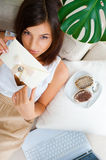 Cute young woman. Delighted woman reading a greeting card sitting on the sofa at home and eating tasty cakes. Top View stock image