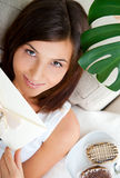 Cute young woman. Delighted woman reading a greeting card sitting on the sofa at home and eating tasty cakes. Top View stock photography