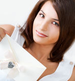 Cute young woman. Delighted woman reading a greeting card sitting on the sofa at home. Top View stock photos