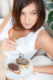 Cute young woman. Smiling brunette woman eating some cake in the living room in her apartmant stock image
