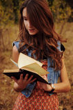 Cute young woman in the autumn forest reading a book Stock Photography