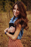 Cute young woman in the autumn forest reading a book. Cute young woman with long auburn hair in the autumn forest reading a book Stock Images