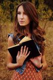 Cute young woman in the autumn forest reading a book Royalty Free Stock Image
