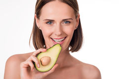Cute young woman with avocado Royalty Free Stock Photos