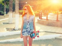 Cute young woman backlit standing with skateboard in her hands royalty free stock photo