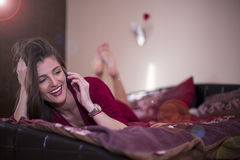 Cute young woman in bed talking on a phone Stock Photo