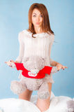 Cute young woman in a bed with a teddy bear Stock Photos