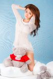Cute young woman in a bed with a teddy bear Royalty Free Stock Photography