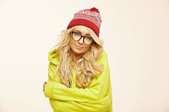 Cute young woman with blonde hair self-embrace, stands on white isolated background, wears red cap and yellow sweatshirt. Portrait of smiles girl stock images