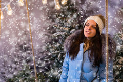 Cute young woman in blue down jacket standing in a snow-covered Stock Photo