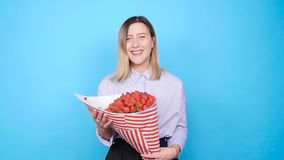 A cute young woman with a bouquet of strawberries stock footage