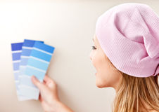 Cute young woman choosing colors for painting room Royalty Free Stock Images