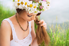 Cute young woman with circlet of camomile braiding her hair. At the riverside Stock Photos