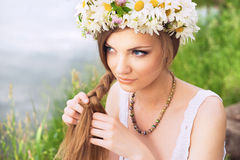 Cute young woman with circlet of camomile braiding her hair at t. He riverside stock photos