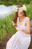 Cute young woman with circlet of camomile. At the riverside stock images