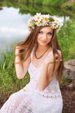 Cute young woman with circlet of camomile. At the riverside stock image