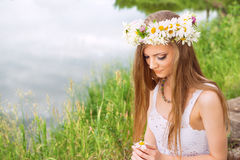 Cute young woman with circlet of camomile. At the riverside stock photography
