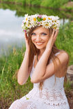 Cute young woman with circlet of camomile Stock Images