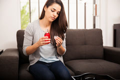 Cute young woman with cough. Pretty young woman about to take some cough syrup at home Stock Image