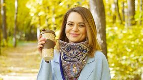 Cute young woman with cup of coffee in the autumn park stock footage