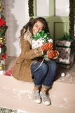 Cute young woman at decorated house with presents Royalty Free Stock Photos