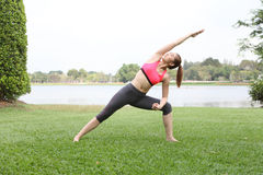 Cute young woman doing physical exercises on lawn Royalty Free Stock Photos