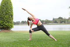 Cute young woman doing physical exercises on lawn Stock Images