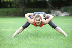 Cute young woman doing physical exercises on lawn Royalty Free Stock Images
