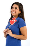 Cute young woman dreaming of love. Standing holding three red hearts in her hands looking up into the air with a dreamy faraway look and big smile of pleasure Royalty Free Stock Photography