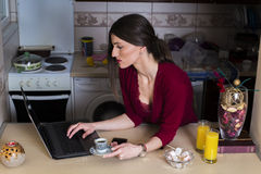 Cute young woman drinking coffee in kitchen and working on laptop Stock Image