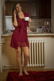 Cute young woman drinking coffee and talking on a phone Stock Photo