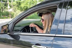 Young woman driving black SUV checking rear view mirror royalty free stock photo