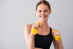 Cute young woman with dumb bells. Healthy and wealthy. Happy and positive young woman holding dumb bells in hands while standing on isolated grey background Stock Image