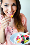 Cute young woman eating jelly candies with a fresh smile Royalty Free Stock Photography