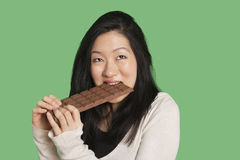 Cute young woman eating a large chocolate bar over green background Stock Image