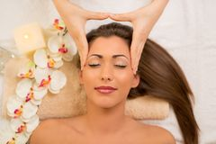 Head Massage. Cute young woman enjoying in head massage with her eyes closed. Top view Stock Photography