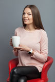 Cute young woman is enjoying hot tea. Portrait of attractive girl drinking coffee and relaxing. She is sitting in a red chair and smiling. The lady is looking at Stock Images