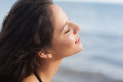 Cute young woman with eyes closed at beach Royalty Free Stock Images
