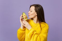 Cute young woman in fur sweater keeping eyes closed holding, kissing half of fresh ripe avocado isolated on violet. Pastel background. People vivid lifestyle royalty free stock image