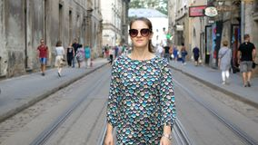 Cute young woman with glasses is walking along the old city. Beautiful dress with circles. The brunette spends her stock video footage
