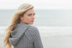 Cute young woman in gray knitted jacket on beach Royalty Free Stock Photography