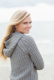 Cute young woman in gray knitted jacket on beach Stock Photo